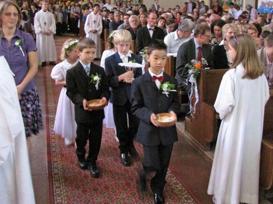 Kinder bringen Brot und Wein zum Altar.