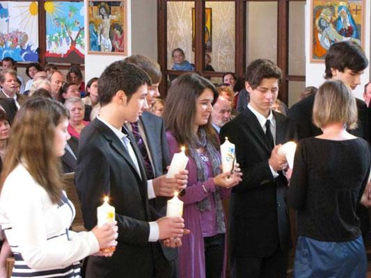 Die 11 Firmlinge kommen mit ihren Kerzen zum Altar und stellen sich im Halbkreis auf. Die Firmbegleiter entzünden die Kerzen mit dem Licht der Osterkerze.