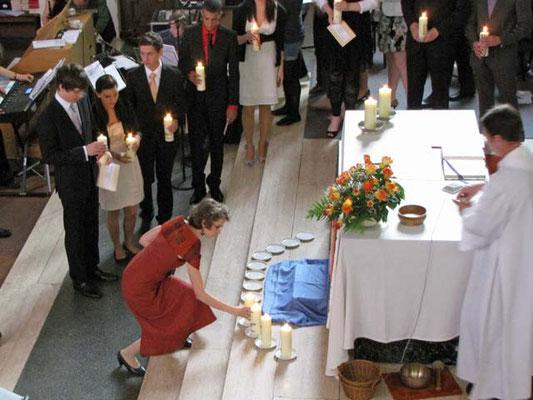 Die 13 Firmlinge stellen ihre Kerzen vor dem Altar auf. Die brennenden Kerzen bilden bis zum Ende der Messe ein stimmungsvolles Bild.