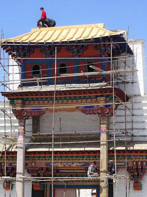 Der Architekt auf dem Dach und die Maler am streichen.