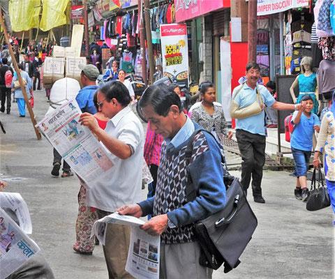 Zeitungsleser vor dem Zeitungsverkäufer