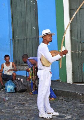 Er spielt das Capoeira Instrument Berimbau.