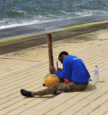 Er pflegt seine Kora. (Harfeninstrument aus Senegal)