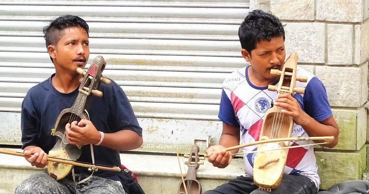 Strassenmusikanten mit Streichinstrument aus einem Stück Holz geschnitzt