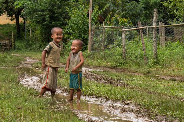 Laotische Jungs spielen in den Regenpfützen