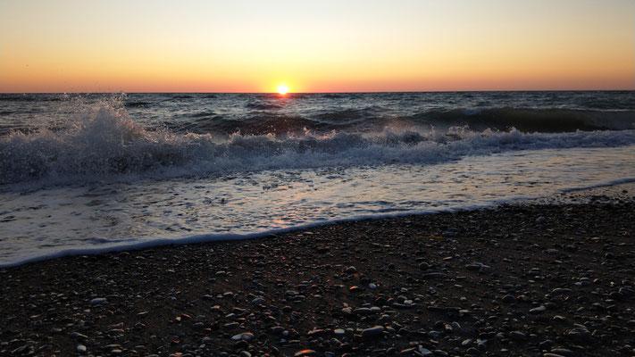 Sonnenuntergang und Pizza essen am Strand
