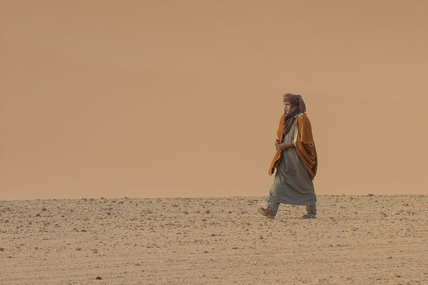 Nomad walking in the dunes / Libya