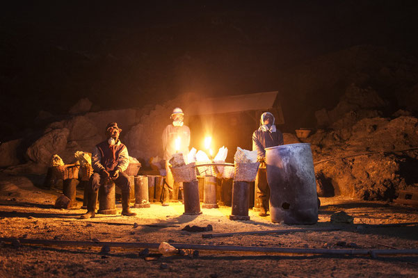 Sulfur miners while resting before climb up the crater of the volcano with their loads during their night shift