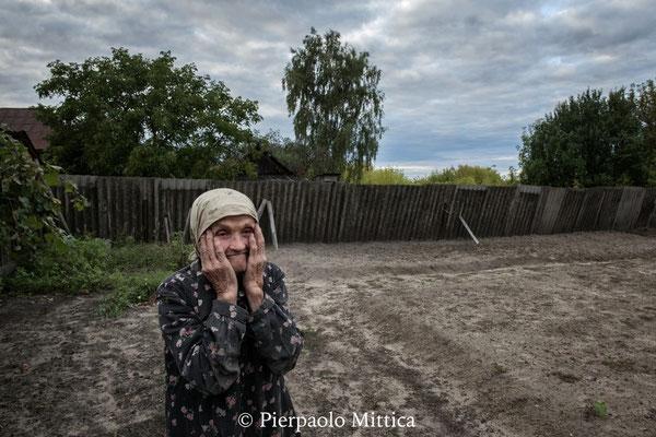 Maria Shovkuta, 88 anni, nel giardino di casa sua, villaggio di Opachici. Maria sta mostrando il suo giardino, dove aveva l'abitudine di coltivare ortaggi per le sue esigenze, ma ora è sempre più anziana ed è sempre più difficile badare all'orto
