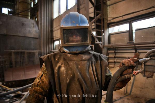 Lo scafandro che indossa il sabbiatore protegge dalle particelle di sabbia ma non dall'aerosol radioattivo sprigionato dalla pulitura delle superfici dei metalli contaminati