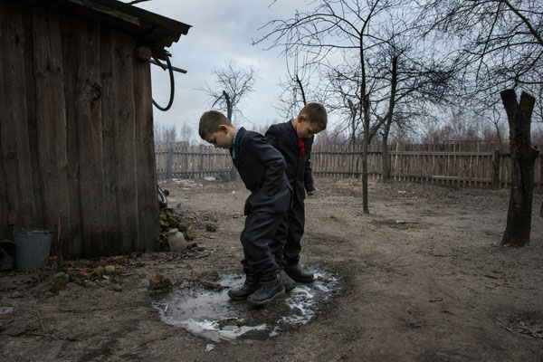 Vladik, 7 years old and Igor, 6 years old, live in Radinka. Here they are waiting in the garden of their home to go to school.