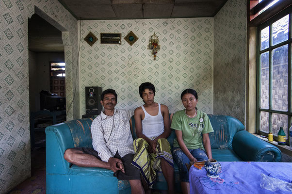 Samiri with his son and wife at home. They live in Sumberwatu village