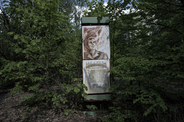 A propaganda sign surrounded by nature in what was once an avenue for walking in the ghost town of Pripyat.