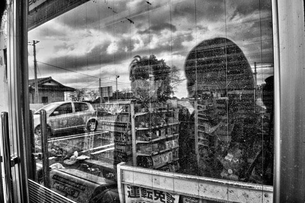 "Yoshida and his wife Mutzumi looking inside the market where they met the first time, Tomioka City, Fukushima ""No-Go Zone"", Japan."