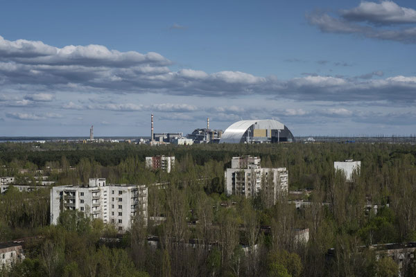 The Chernobyl nuclear power plant with the new sarcophagus under construction seen from the ghost town of Pripyat.