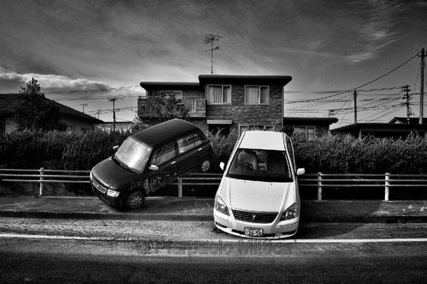 """abandoned cars parked by the tsunami, Odaka city, Fukushima """"No-Go Zone"""", Japan."""
