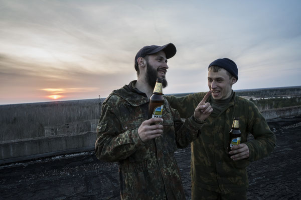 Jimmy and another stalker laughing and drinking beer on the roof of a building in the ghost town of Pripyat.