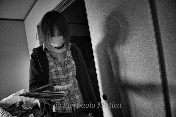 """Mutzumi feels depressed collecting her personal belongings in her abandoned house in the Exclusion zone.  Namie city, Fukushima """"No-Go Zone"""", Japan."""