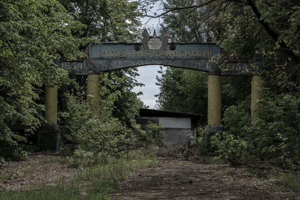 The entrance arch, submerged by vegetation, of the abandoned city of Polesskoe, located within the Chernobyl exclusion zone.