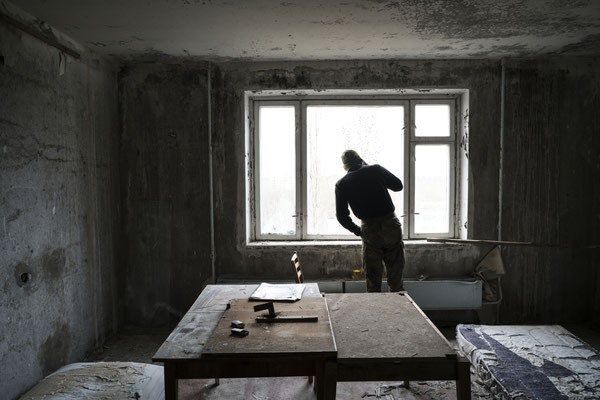 Jimmy checking from the window in his apartment in Pripyat if police is around before leaving