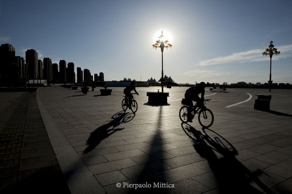An empty square with two bikers in the new district of Kangbashi, Ordos