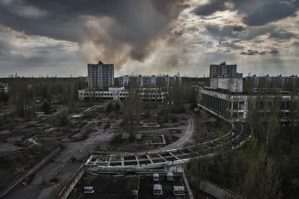 The forest burns behind the ghost city of Pripyat. One of the greatest dangers existing in the exclusion zone are fires. Fire burns trees raising radioactive ash that is spread in the air, causing a new nuclear fallout.