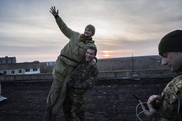 Stalkers having fun during the sunset in a roof of a building of the ghost town of Pripyat