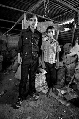 Raju with his boss. This shop owners has 15 tokai children working for him. Tonghi slum, Dhaka.