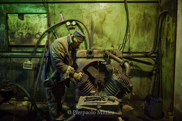 Pavel fixing the engine of the ventilation system inside the warehouse for the recycling of the radioactive metals