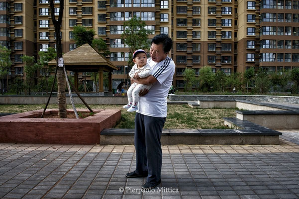 Mr. Lin with his grandson in the social houses in the new district of Kangbashi, Ordos