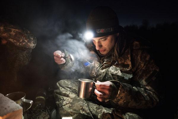 Maxim preparing a cup of tea to get warmer in the abandoned village of Rudnya Veresnya before heading to Pripyat.