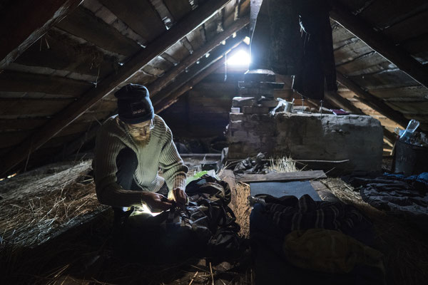 Sasha preparing for the night in the abandoned village of Rudnya Veresnya. Stalkers usually sleep in the garret, to stay safe from wild animals now abundant in the zone: wolves, boars, bears and mooses – mices and ticks keep them good company, anyway