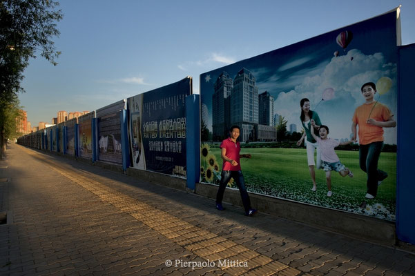 A pedestrian passes in front of billboards that promise a happy life in new and never completed buildings