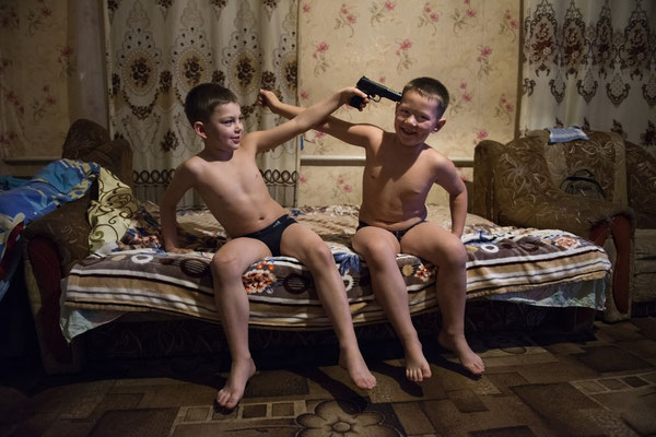 Igor and Vladik playing before going to bed at their home in Radinka