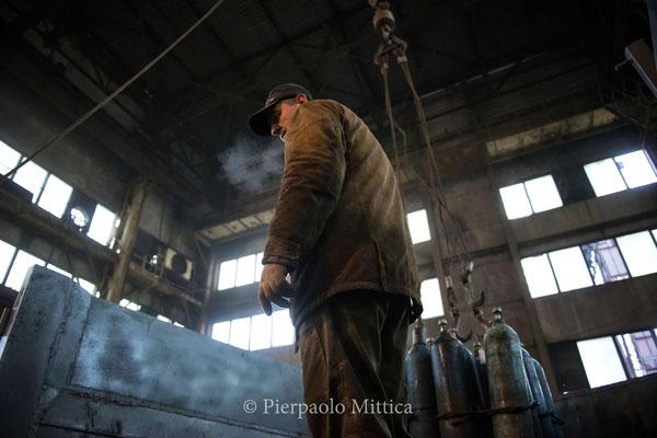 Un lavoratore mentre scarica dal camion le bombole ad aria compressa per il processo della sabbiatura