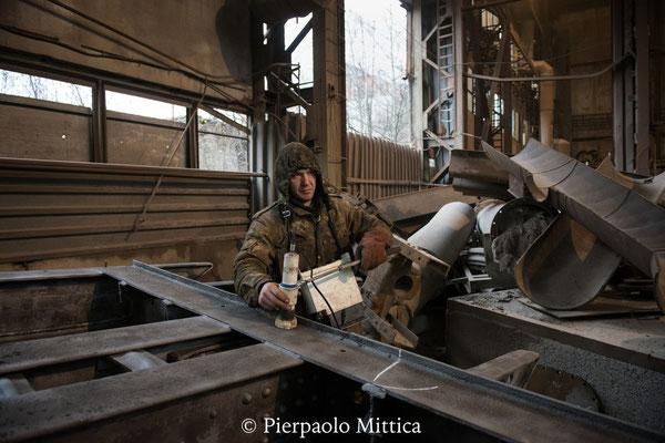 Yuriy mentre controlla il livello di contaminazione dei metalli riciclati dopo la sabbiatura