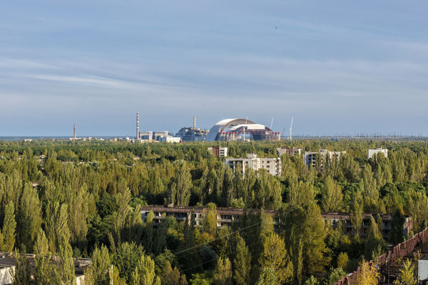 The abandoned city of Pripyat invaded by nature. In the background the Chernobyl nuclear power plant.