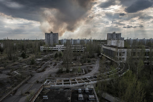 A fire burns behind the abandoned city of Pripyat. One of the greatest dangers in the exclusion zone are fires because they throw the contamination accumulated in the plants back into the air, causing a new radioactive fallout.