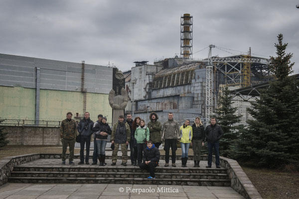 Tourists while taking a picture in front of sarcophagus of reactor number four, Chernobyl nuclear power plant