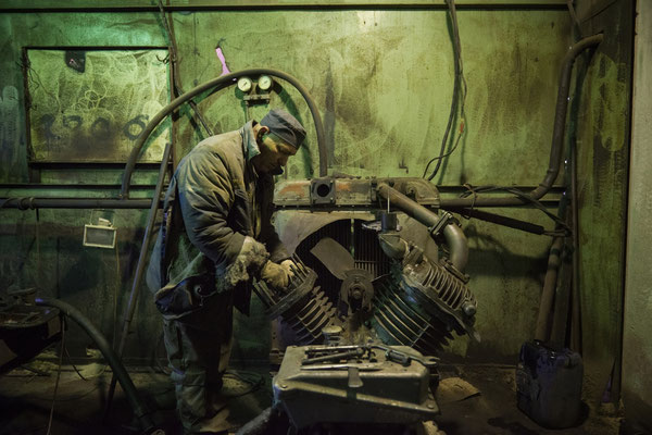 Pasha while repairing an engine that is used to force ventilation in the radioactive scrap metal recycling facilities. Chernobyl Exclusion Zone.