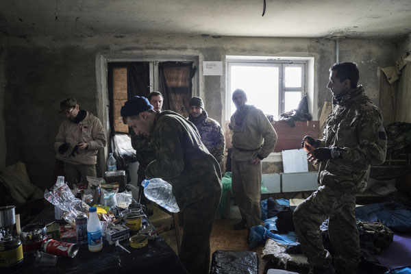 A stalker distributing to the other members of his group the water collected in the flood basement of a building in the ghost town of Pripyat