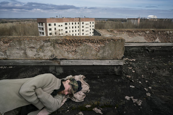 Sasha sleeping on the roof of a building in the ghost town of Pripyat. Chernobyl and the unfamous Reactor 4 are on his right, just three kilometres away