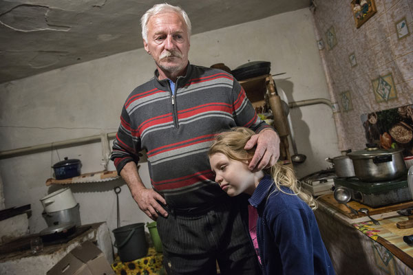 Dimitri 60 years with his nephew Vlada 7 years, in his home in the village of Marianovka. Vlada lives in Kiev but sometimes her grandfather Dimitri brings her illegally in his house inside the zone to stay with him some days. Chernobyl Exclusion Zone.