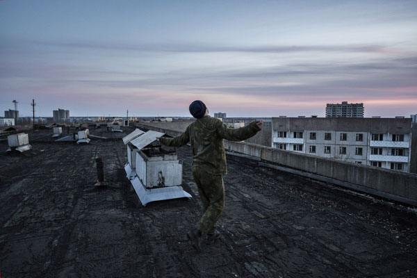 A stalker dancing at sunset on the roof of a building of the ghost town of Pripyat.