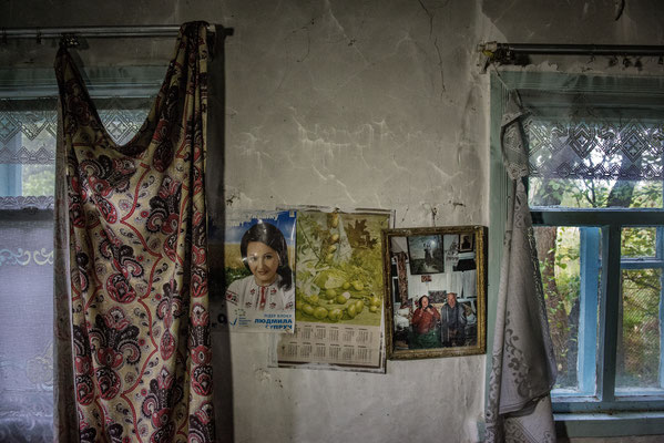 The photo of Nikolai and Anastasia in the wall of their home. Nikolai died two years ago and his son took his mother away from the area to live with him in Kiev. Now their home is abandoned, the photo is their last memory in their house. Paryshev