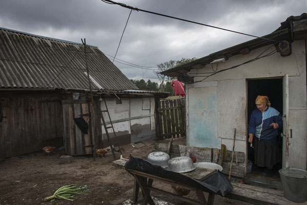 Maria Ilchinko, 79 years old, in front of the chicken coop after giving food to the chickens. Now in this village only 8 elderly lives. Kupovate, the Chernobyl Exclusion Zone