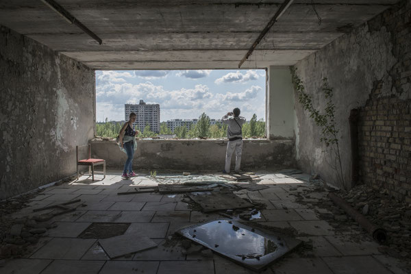Former inhabitants of the city of Pripyat taking souvenir photos from the top floor of the Polessya hotel, in the main square of the city of Pripyat.