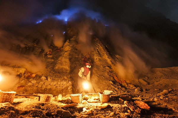 A miner while collecting chunks of sulphur in the volcano crater during his night shift