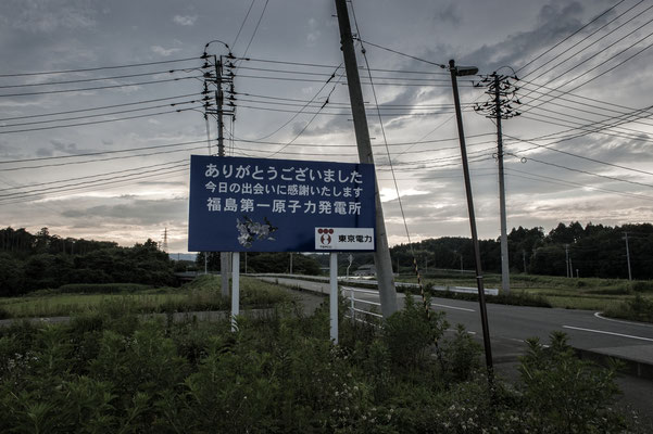 """The roadsign put by Tepco at the exit of Fukushima Daiichi nuclear plant tells: """"thank you for your visit, it was great to meet you, hope to see you soon.TOKYO DENRYOKU (TEPCO)"""". Fukushima No-Go Zone."""