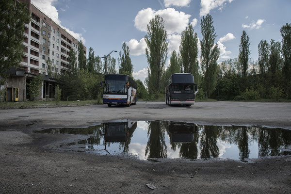 Buses parked in the main square of the ghost town of Pripyat waiting for the former inhabitants to visit their city.